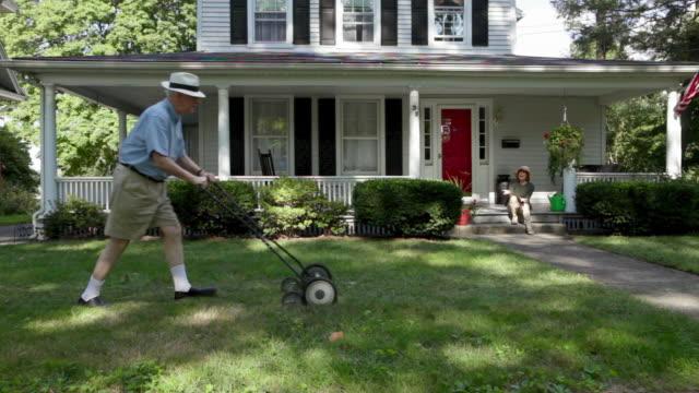 vídeos de stock, filmes e b-roll de senior man mowing front lawn - homens idosos