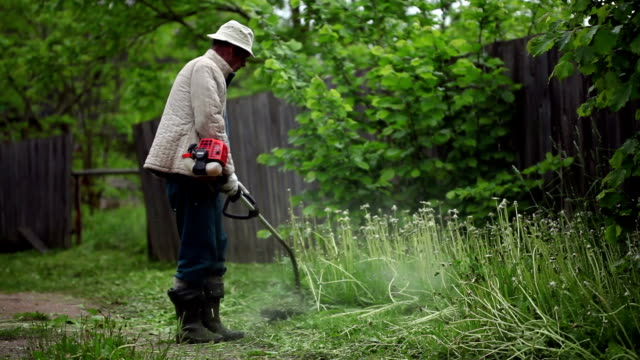 senior man mowing the grass with trimmer - gardening glove stock videos & royalty-free footage