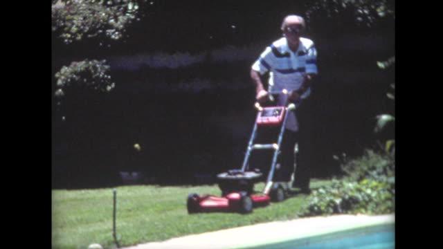 1976 senior man mows lawn near pool - suburban stock videos & royalty-free footage