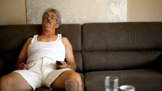 senior man napping on couch - sdraiato video stock e b–roll