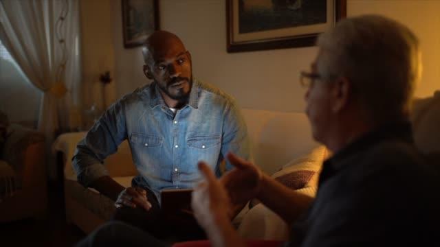 vídeos de stock, filmes e b-roll de homem sênior em uma reunião com o conselheiro em casa - orientação