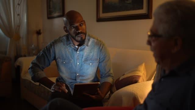 vídeos de stock, filmes e b-roll de homem sênior em uma reunião com o conselheiro em casa - profissional de saúde mental