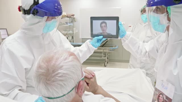 病院icuで孫とビデオ通話中の先輩男性 - レスピレーターマスク点の映像素材/bロール