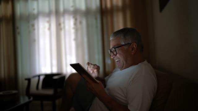 stockvideo's en b-roll-footage met hogere mens op een video die gebruik maakt van een digitale tablet thuis - 65 69 jaar