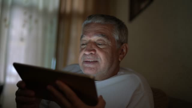 senior man on a video calling using a digital tablet at home - video call stock videos & royalty-free footage