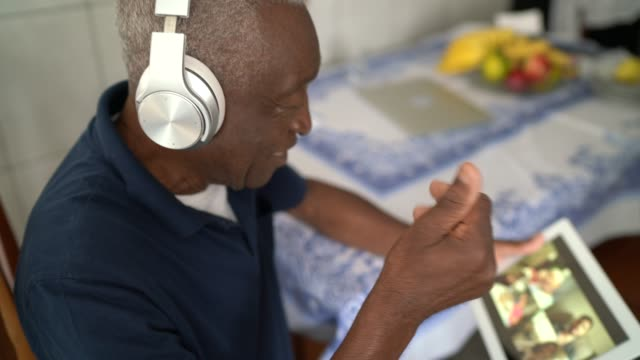 senior man on a video calling using a digital tablet at home - headphones stock videos & royalty-free footage