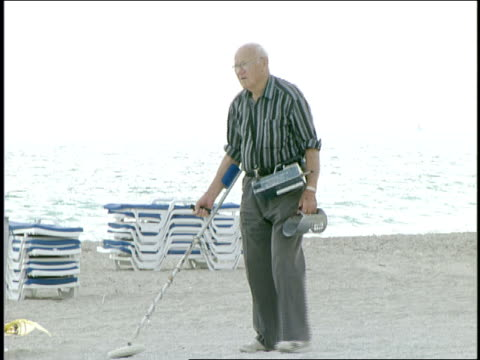 senior man on beach with metal detector in miami, florida - 宝探し点の映像素材/bロール