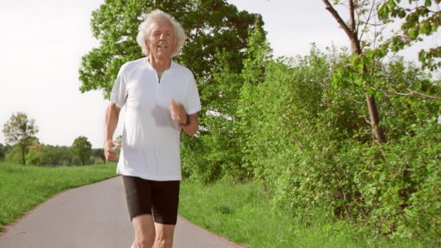 vídeos de stock, filmes e b-roll de slo mo t homem sênior em suas corridas diárias - 65 69 anos