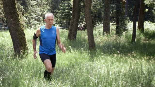 SLO MO DS Senior man on his run through forest
