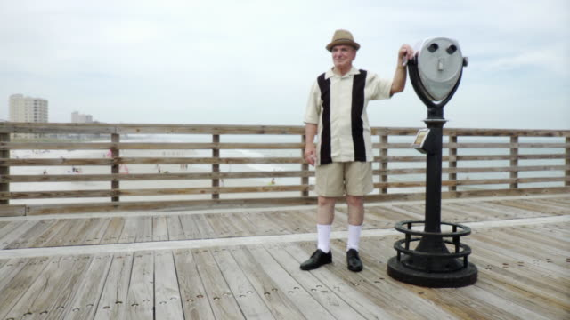 WS PAN Senior man on pier leaning against coin operated binoculars / Jacksonville Beach, Florida, USA