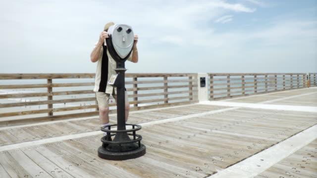 vídeos de stock, filmes e b-roll de ws senior man on pier looking through coin operated binoculars / jacksonville beach, florida, usa    - looking through an object