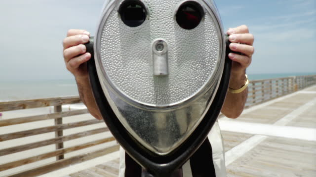 ms tu senior man on pier looking through coin operated binoculars / jacksonville beach, florida, usa   - canocchiale video stock e b–roll