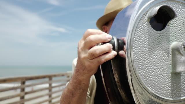 vídeos de stock, filmes e b-roll de cu senior man on pier looking through coin operated binoculars / jacksonville beach, florida, usa   - looking through an object