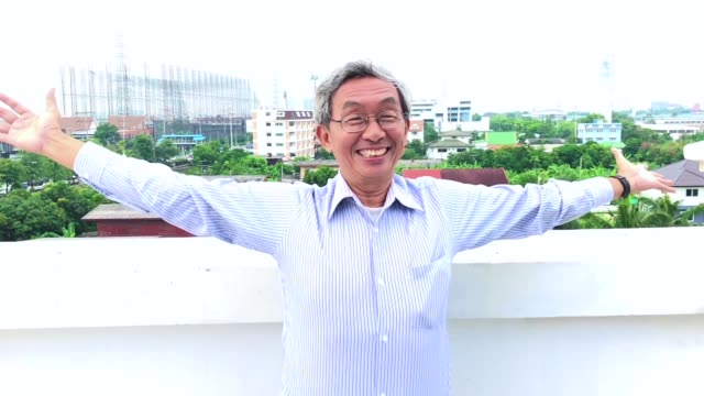 senior man opening arms on the roof. cityscape in background - open arms stock videos & royalty-free footage