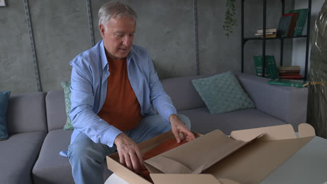 senior man opening delivery package at home - grey hair stock videos & royalty-free footage