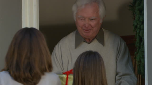 CU, Senior man opening doors and receiving Christmas presents from two girls (10-11), Los Angeles, California, USA,