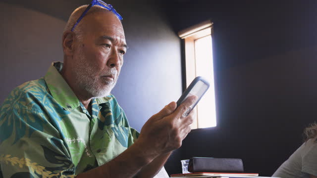 a senior man operating a mobile phone at a restaurant where he went to eat - 神奈川県点の映像素材/bロール