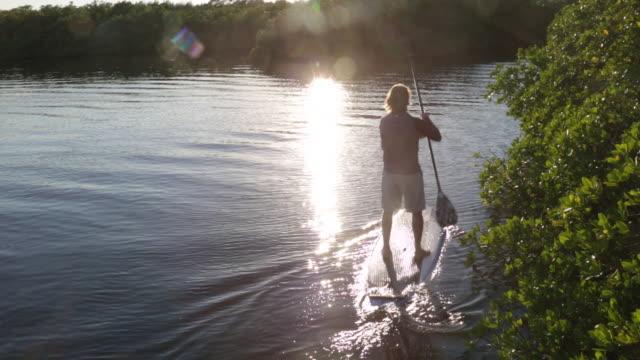 WS Senior man paddle boarding on lake.