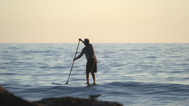 stockvideo's en b-roll-footage met ws senior man paddleboarding around some rocks in the ocean - peddelen