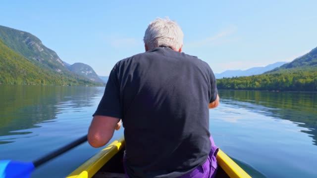 vidéos et rushes de un homme aîné pagaie un canot sur un lac calme bohinj - pagayer