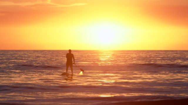 ws senior man paddling into the sunset - adventure stock videos & royalty-free footage