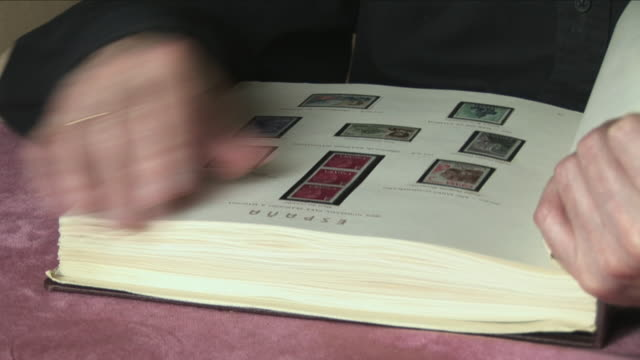 cu tu senior man passing pages of stamp collection book, bilbao, spain - 集める点の映像素材/bロール