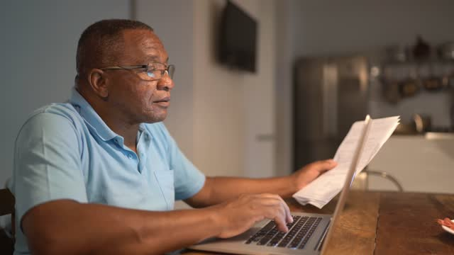 senior man paying bills or doing home finances on laptop - document stock videos & royalty-free footage