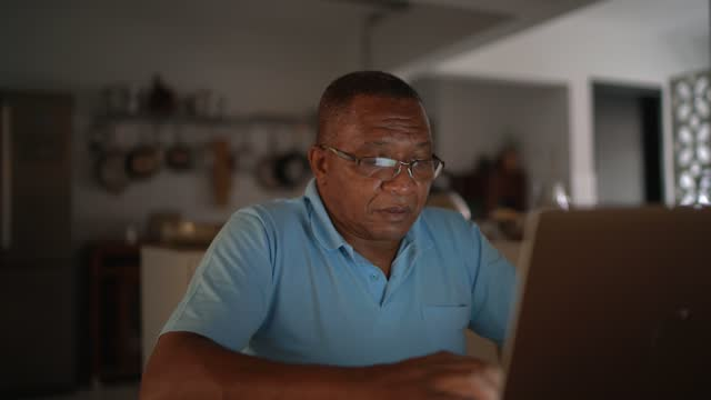 senior man paying bills or doing home finances on laptop - e mail stock videos & royalty-free footage