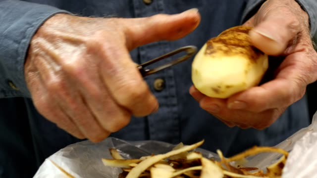 Senior man skalar färsk potatis med en potatisskalare.