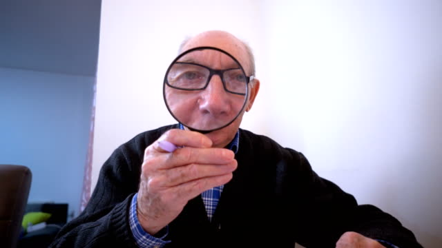 senior man peering through a magnifying glass - magnifying glass stock videos & royalty-free footage