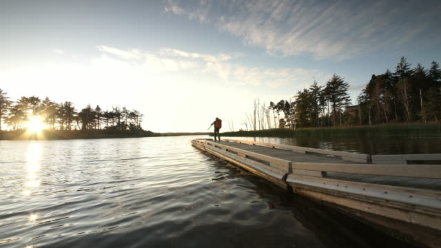 Senior man photographer walking on Boat Dock on the lake and setting up a tripod to take a picture