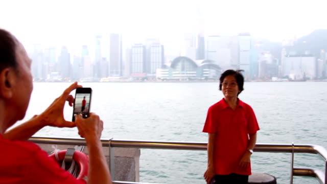 vídeos de stock, filmes e b-roll de senior man photographing with mobile phone while senior women posing for photograph, hong kong, china - kowloon