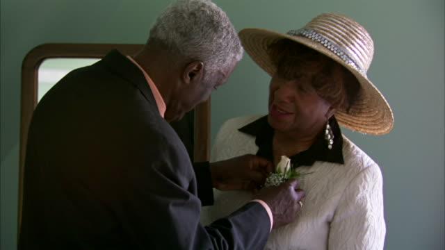 MS Senior man pinning corsage on senior woman in hat / they kiss / Halifax, Nova Scotia