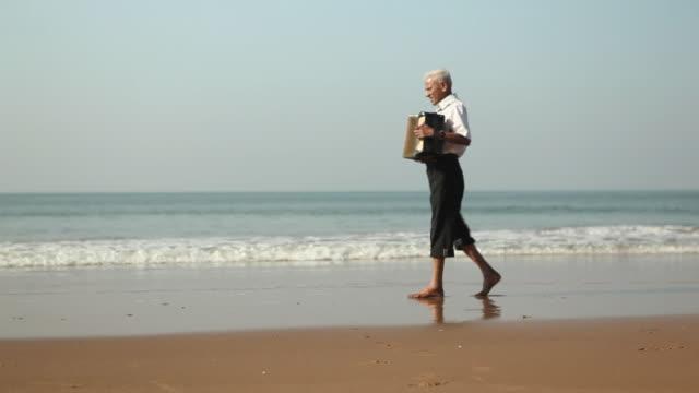 vídeos y material grabado en eventos de stock de senior man playing accordion on the beach - acordeonista
