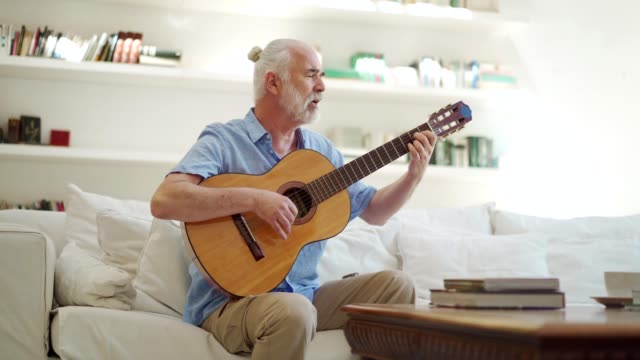 vídeos de stock, filmes e b-roll de homem sênior que joga a guitarra acústica - dedilhando instrumento