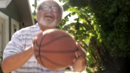 Senior man playing basketball outdoors