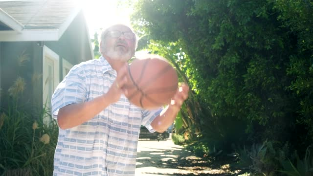 Seniorenmann spielt Basketball im Freien