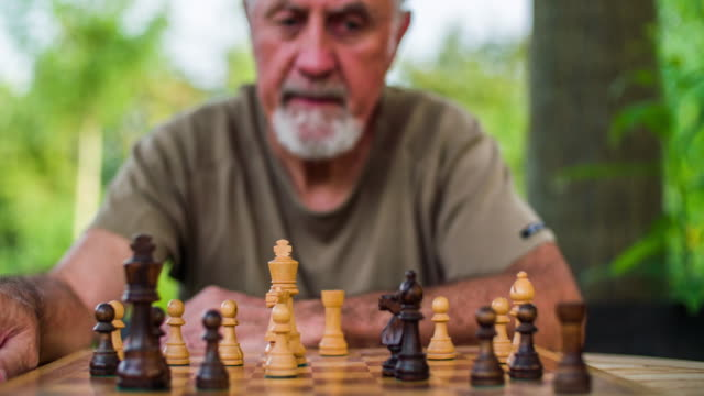 senior man playing chess - chess stock videos & royalty-free footage