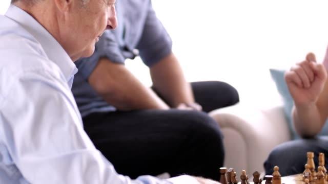 stockvideo's en b-roll-footage met senior man spelen schaken met zijn kleinzoon - spelletjesavond