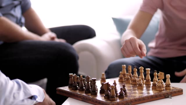 senior man playing chess with his grandson - scacchi video stock e b–roll