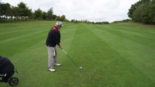 a senior man playing golf. - ゴルフのスウィング点の映像素材/bロール