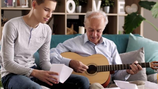 senior mann, der gitarre für seine familie spielt - großvater stock-videos und b-roll-filmmaterial