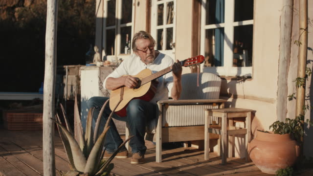 senior man playing guitar in front of house - composer stock videos & royalty-free footage