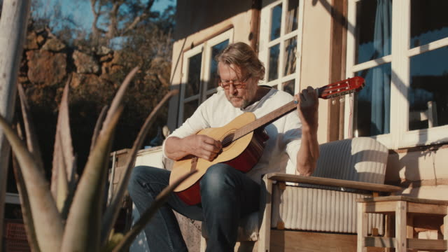 senior man playing guitar in front of house - pensionierung stock-videos und b-roll-filmmaterial