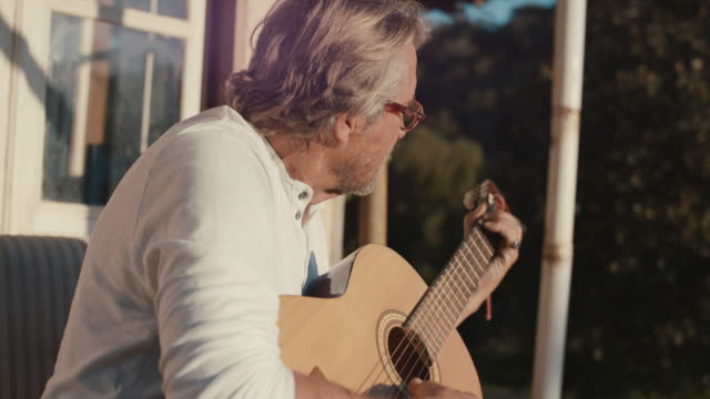 senior man playing guitar in sun - musical instrument stock videos & royalty-free footage