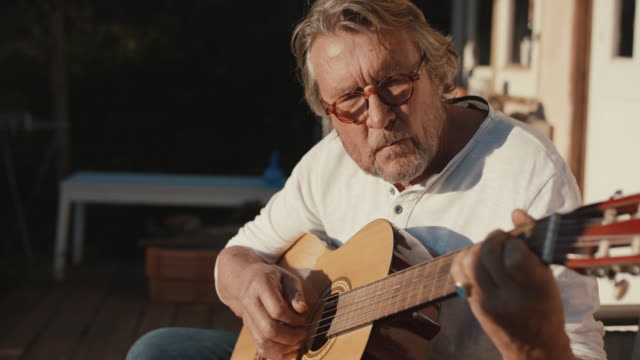 stockvideo's en b-roll-footage met senior man playing guitar in sun - muzikant