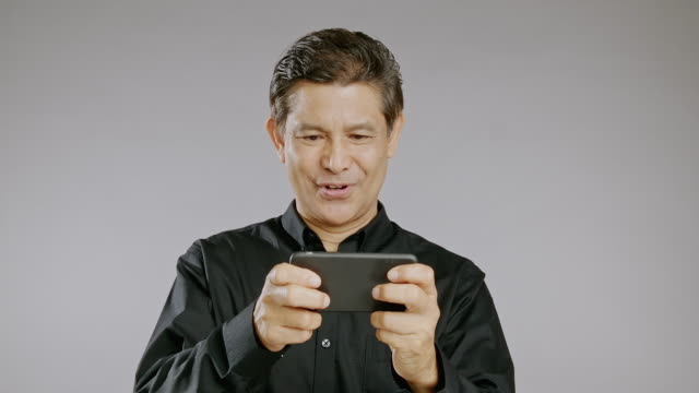 senior man playing his mobile game, smile, win, isolated in grey background. asian man in black shirt - black shirt stock videos & royalty-free footage