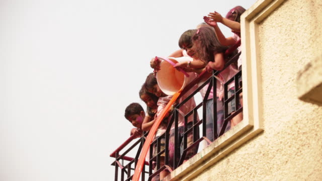 senior man playing holi festival with his grandchildren at roof top  - balcony stock videos & royalty-free footage