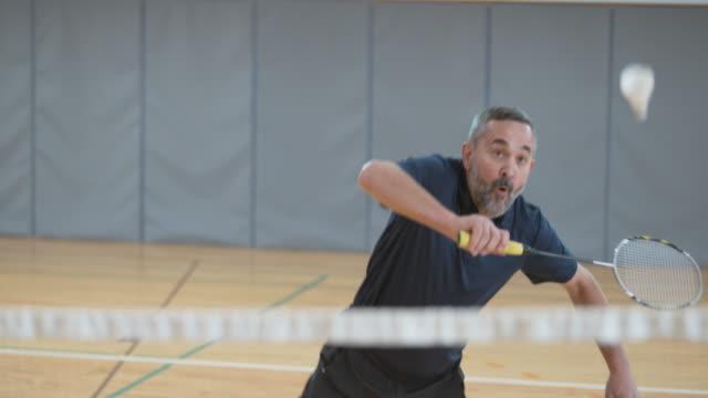 Senior man playing indoor badminton