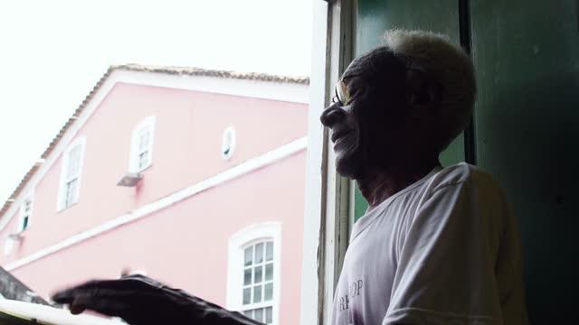 vídeos de stock, filmes e b-roll de idoso brincando de pandeiro na varanda de sua casa - sacada
